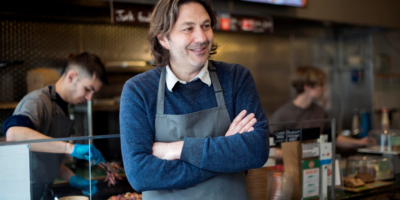 David Arkin stands in front of his shop counter, wearing an apron