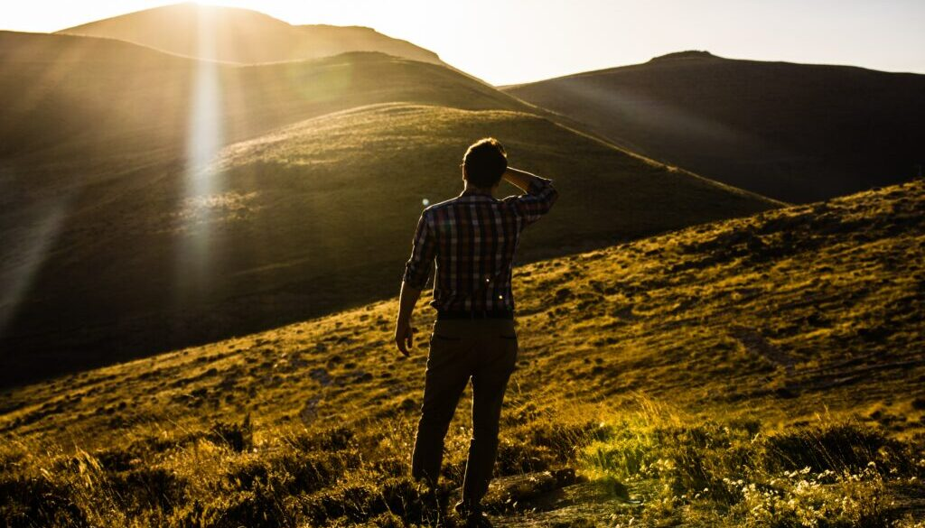 A man stands in a field, looking into the horizon of a newly discovered land, Photo by saeed mhmdi on Unsplash