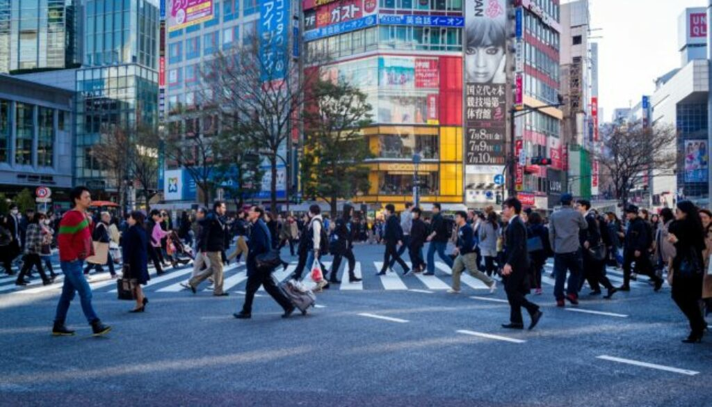 Busy commuters in Japan pass by outdoor advertising, Photo by Cory Schadt on Unsplash