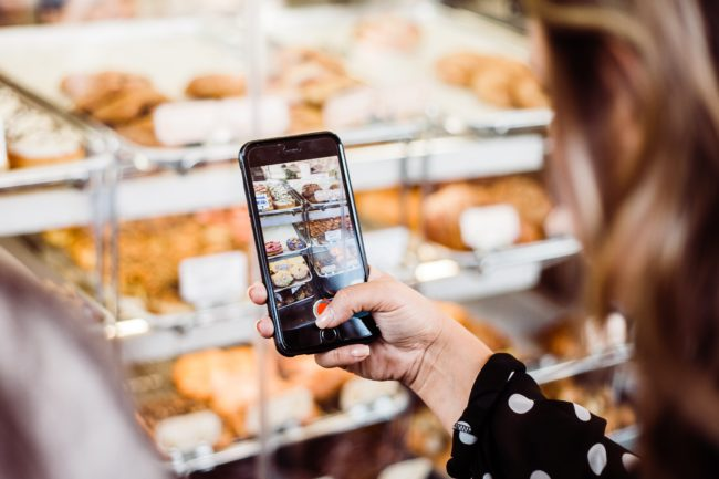 A customer uses free wifi to take pictures for social media, Photo by Jenna Day on Unsplash